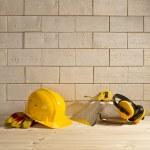 Brick background, helmet and trowel — Stock Photo #23525705