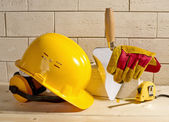 Brick wall, helmet and trowel — Stock Photo