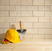 Brick background, trowel and helmet — Foto Stock
