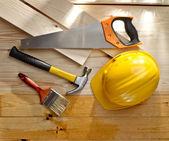 Wood floor with a brush, saw, hammer and helmet — Foto de Stock