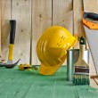 Green wood floor with a brush, paint, saw and yellow helmet — Stock Photo #34650583
