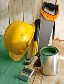 绿色木地板用画笔,锯子,锤子和头盔 — 图库照片
