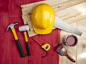 Red wood floor with a brush, paint, hammer and yellow helmet — Stock Photo