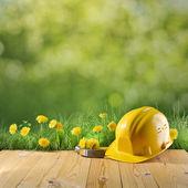 Construction helmet on green nature background — Stock Photo