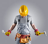 Builder in a helmet with a hammer and a wrench — Stock Photo
