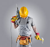 Builder in a helmet with a hammer and a drill — Stock Photo