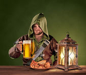 Medieval man in a tavern with a beer on the vintage background — Stock Photo