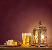 Old lantern with beer, cheese and bread on vintage background — Stock Photo