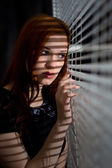 Beautiful girl looking through the blinds — Stock Photo