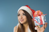 Girl in red dress and santa claus hat — Stock Photo