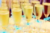 Glasses of champagne with blue wedding ribbons on the table. Sparkling beverage — Stock Photo