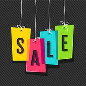 Sale tag on colored hanging labels — Cтоковый вектор