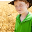 Young midwestern  cowboy stands in wheat field on farm - Stock Photo