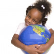 Pretty little girl hugs the globe — Stock Photo #21356763