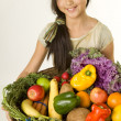 Stock Photo: Young girl offers a basket of fruits and vegetables