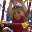 Hispanic little boy swinging from monkey bars — Stock Photo