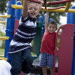 Hispanic brothers swinging from monkey bars - Stock Photo