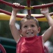 Stock Photo: HIspanic little boy swinging from monkey bars