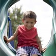 Stock Photo: Hispanic little boy on playground sliding