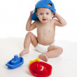 Baby boy wearing a blue cap playing with plastic toys — Stock Photo #21359567