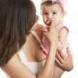 Little baby girl chewing mother's finger — Stock Photo