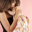 Mother hugging her baby daughter on a pink background — Stock Photo