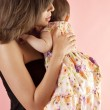 Stock Photo: Mother hugging her baby daughter on a pink background