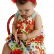 Baby girl wearing a pretty floral dress sitting in the tiny chair — Stock Photo