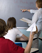 School boy playing with paper plane in class — Stock Photo