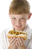 Redheaded boy holding hotdog — Stock Photo