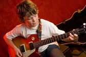 Child rock star plays electric guitar — Stock Photo