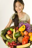 Young girl offers a basket of fruits and vegetables — Stock Photo