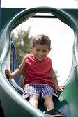 Hispanic little boy on playground sliding — Stock Photo