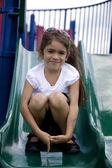 Hispanic little girl on playground sliding — Stock Photo