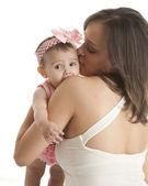 Mother hugging her teething baby daughter — Stock Photo