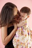 Mère étreindre et embrasser sa fille — Photo