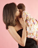 Young mother hugging and kissing her baby — Stock Photo