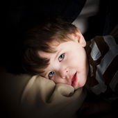 Little boy with blue eyes and brown hair resting on a pillow — Stock Photo