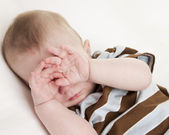 Sleepy caucasian baby boy rubbing his eyes — Stock Photo