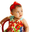 Pouting baby girl in colorful dress — Stock Photo