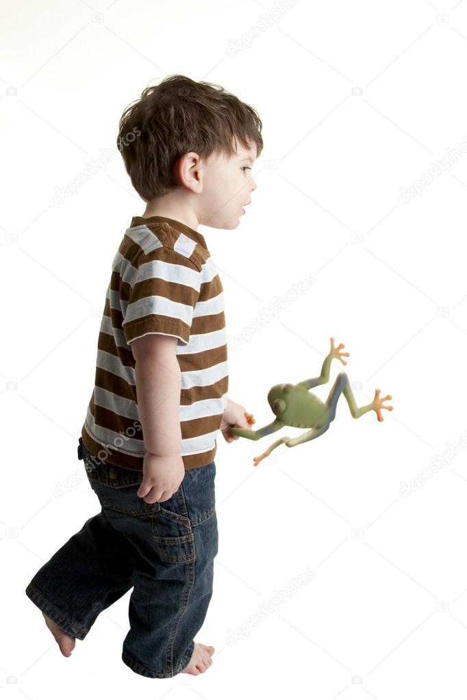 Kleiner junge spielt mit kunststoff frosch spielzeug