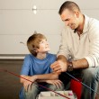 Young man helping adolescent boy with fishing equipment — Stock Photo #21360449