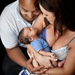 Mother and father cradling their newborn baby - ストック写真