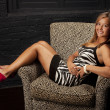 Smiling girl with a beautiful suntanwearing a zebra print dress sitting in  chair — Lizenzfreies Foto