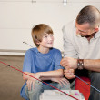 Young man helping adolescent boy with fishing equipment - Stock Photo