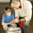 Young man helping adolescent boy with fishing equipment — Stock Photo