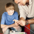 Young man helping adolescent boy with fishing equipment — Stock Photo #21360459