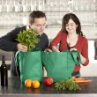 Couple using recycled grocery bags in kitchen — Stockfoto #21360551