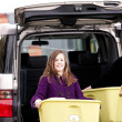 Girl unloading recycle trash at recycling center - Stock Photo