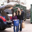 Volunteer employee helping girls at recycling center — Stock Photo #21360631